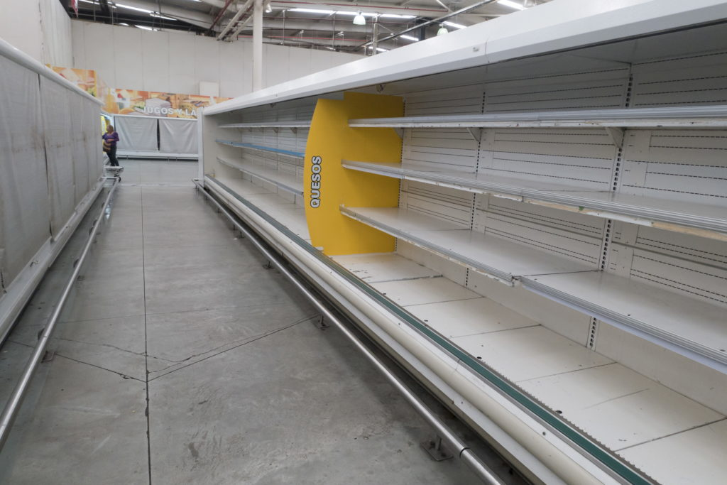 A woman is pictured past empty refrigerator shelves at a Makro supermarket in Caracas August 4, 2015. Picture taken on August 4, 2015. (c)REUTERS/Carlos Garcia Rawlins TPX IMAGES OF THE DAY - RTX1NCIW Pic found at www.pbs.org